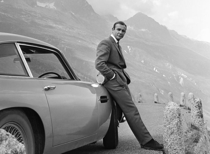 costume homme assis sur une voiture Aston Martin Sean Connery Goldfinger